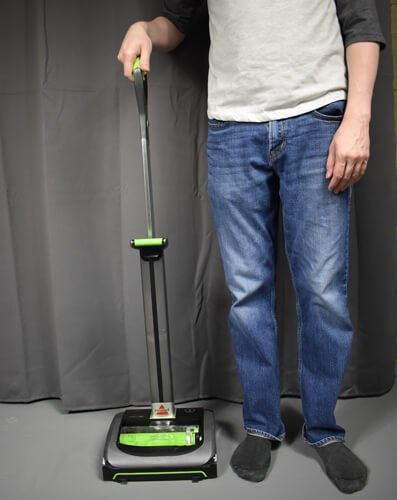The Bissell AirRam 1984 cordless vacuum beside a person