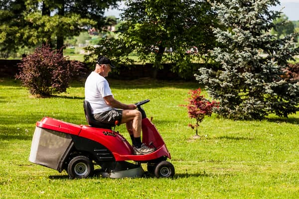 man riding rear engine lawn mower
