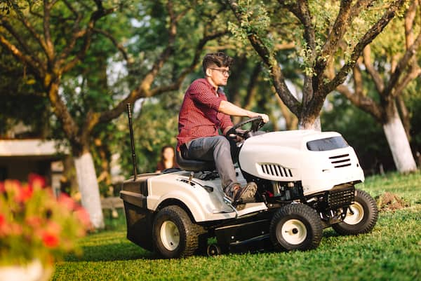 man riding tractor lawn mower