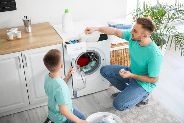 father and son using front load washer