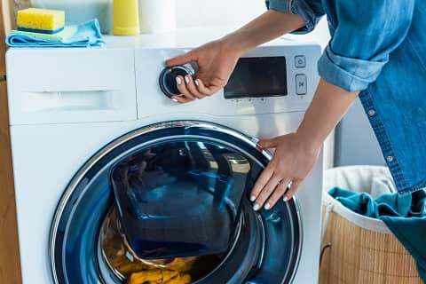 woman using front load washer