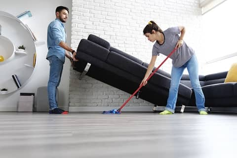 man and women cleaning floor together
