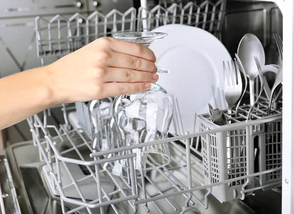 person removing clean glass from dishwasher