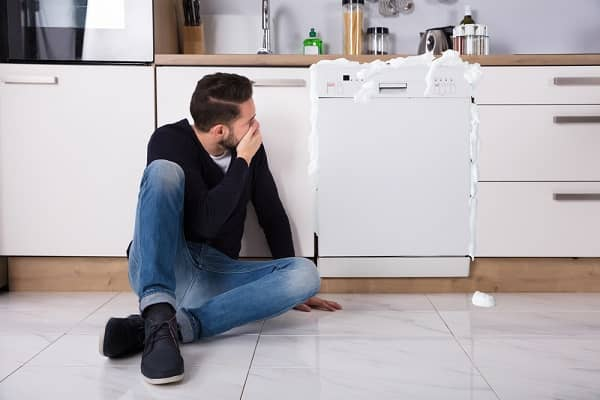 man in awe at malfunctioning dishwasher
